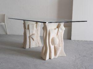 tavolo con piano in cristallo e base in pietra